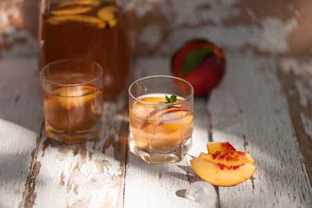 Ice tea and nectarine. Jag, two glasses.  A refreshing summer drink. The concept of summer. On a white wooden  background. Side view Stock Photo