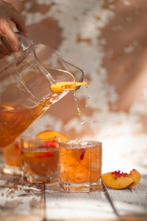 Ice tea with nectarine, peach. In a jug. A woman's hand pours into a glass. A refreshing summer drink. The concept of summer. On a white wooden background. Side view. Place for text