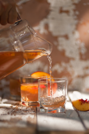 Ice tea with nectarine, peach. In a jug. A woman's hand pours into a glass. A refreshing summer drink. The concept of summer. On a white wooden background. Side view. Place for text Фото со стока - 122057252