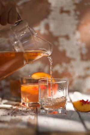 Thé glacé à la nectarine, pêche. Dans une cruche. La main d'une femme se déverse dans un verre. Une boisson estivale rafraîchissante. Le concept de l'été. Sur un fond en bois blanc. Vue de côté. Place pour le texte
