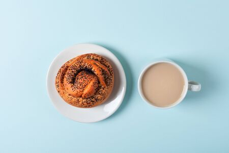 One muffin with poppy seeds and coffee with milk on a blue background Stockfoto