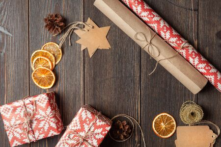 Christmas background or composition. Gift packaging concept in classic Christmas colors. Cones, dried orange, jute ribbon, holiday decorations, craft label on dark wooden background. The view from the top 版權商用圖片
