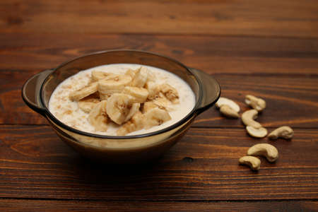 Oatmeal with banana and nuts for breakfast. Oatmeal with fruits, nuts and honey. Healthy food Zdjęcie Seryjne