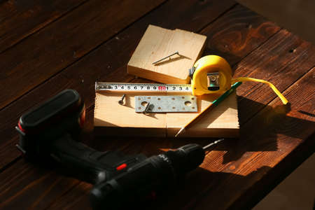 The black screw and is measured by a yellow tape measure with a ruler on a wooden board background. The concept of tools and repair work. Steel screws. Metal screw Banque d'images