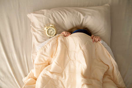 In the early morning, a preschool girl lies in bed under the covers next to the alarm clock. The girl wants to sleep, refuses to get out of bed and go to school.