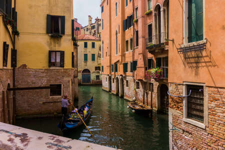 Narrow canals between houses in Venice. Beautiful Ilya city Venice in the summer.