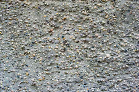 touchstone: small coloreful stones in cement background texture