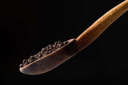 black pepper in wooden spoon closeup photo