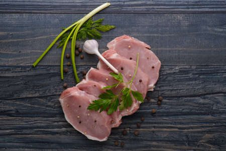 raw meat steak on dark wooden board with spices and garlic photo