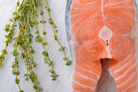 fresh salmon with fresh thyme on a white wooden board photo