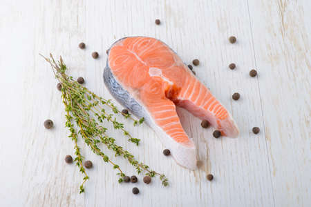 fresh salmon with pepper and thyme on a white board photo