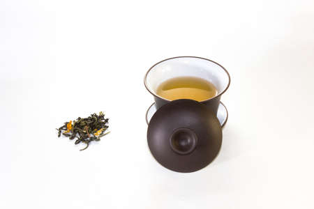rape: snuff cup with green, flower tea, gaivan and a tea cup on a white background ?? Foto de archivo