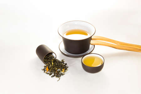 snuff cup with green, flower tea, gaivan and a tea cup on a white background ?? Stock Photo