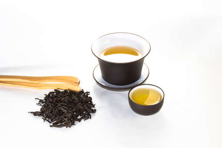 bowl with a cover with tea, a scattering of tea and the Chinese cup on a white background