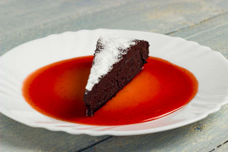 Chocolate decadence pie with strawberry jam on a wooden background