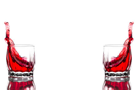 Splash of red juice, wine in a glass ribbed whiskey glass on a white background