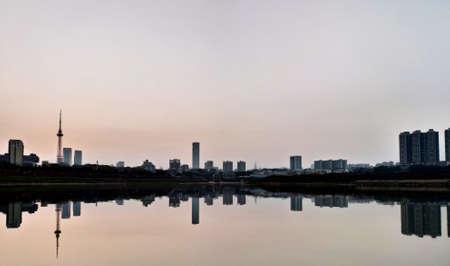 Reflet des bâtiments urbains dans le lac au coucher du soleil