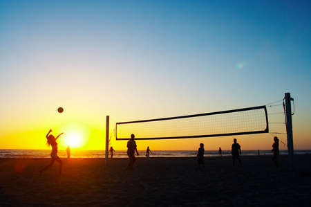 guy on beach: Family playing beach volleyball Stock Photo