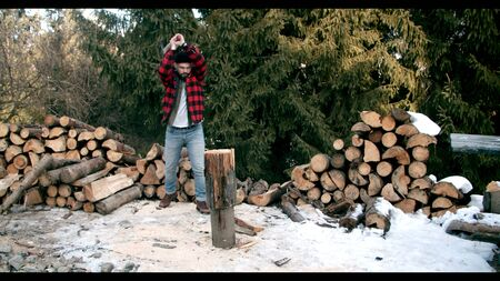 Lumberjack in the snowy winter woodland. Bearded hipster man chopping wood in winter forest.