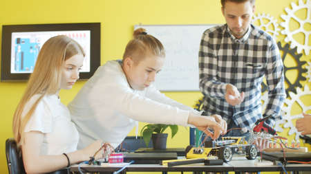 Unrecognizable students assembling car in robotics class