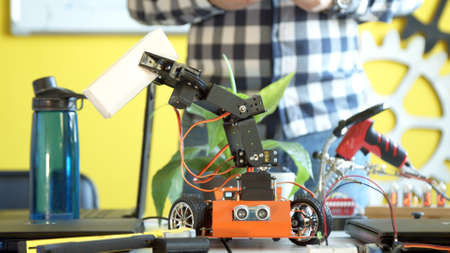 Crop teenager playing with modern robot in class Banco de Imagens