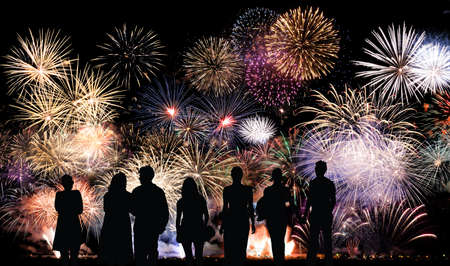 Group of people looks beautiful colorful holiday fireworks, long exposure photo