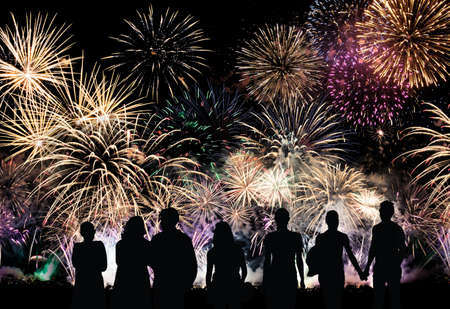 Group of people looks beautiful colorful holiday fireworks, long exposure Stock Photo
