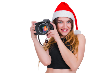 The girl in the hat of Santa Claus with a camera. Young girl photographer Christmas. Christmas selfie