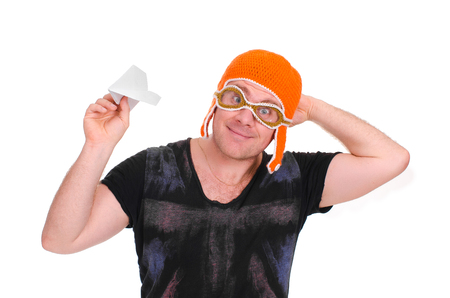 rejoices: Adult male in a childrens knitted hat pilot playing with a paper plane. The man let a paper airplane