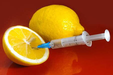 Lemons and Syringe on a red background. Vitamins against medications. Vitamin C
