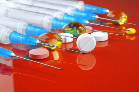 Syringe. Pills. Syringes with tablets on a red background. Injectors with medical preparations.