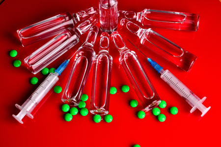 Syringe for subcutaneous injections with glass ampoules and multicolored tablets on an isolated background. Ampoule. Syringes Stock Photo