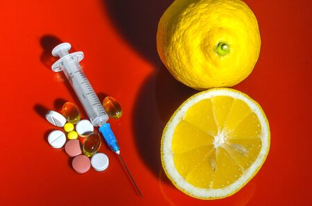 Lemons on a red background with syringes and pills. Medical preparations and vitamin C. Subcutaneous injectors with tablets side by side with lemons on a red background Stock Photo