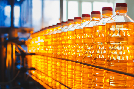 Oil in bottles. Industrial production of sunflower oil. Conveyor line for bottling and packing. Sunflower oil plant