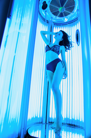 Solarium. Beautiful young girl in a bikini sunbathing in a vertical sunbed. Imagens