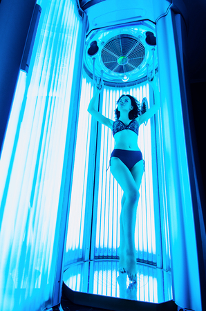 Solarium. Beautiful young girl in a bikini sunbathing in a vertical sunbed. Фото со стока