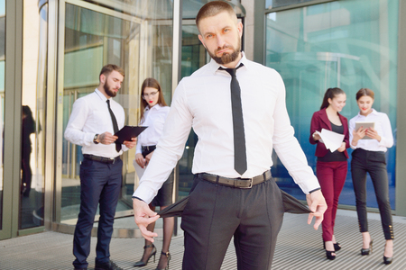 Bankrupt. A young man in black trousers and a white shirt demonstrates his empty pockets in the background of a group of office workers. Dismissal from work