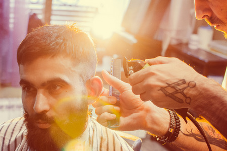 Barber does a haircut on his head with a trimmer to a young handsome guy with a mustache and beard. Mens hair salon.