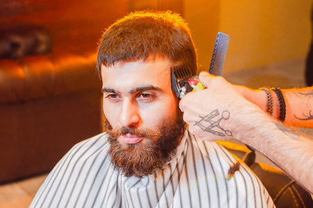 Barber does a haircut on his head with a trimmer to a young handsome guy with a mustache and beard. Men's hair salon.