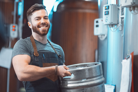 A young brewer in an apron holds a barrel with beer in the hands of a brewery.