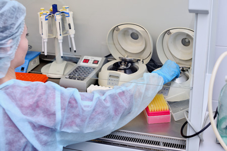 Dna test in the lab. a laboratory technician with a dispenser in his hands is conducting dna analysis in a sterile laboratory behind glass.