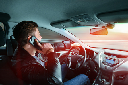 A man talking on a mobile phone in a car at high speed. Driving at high speed. Car travel.