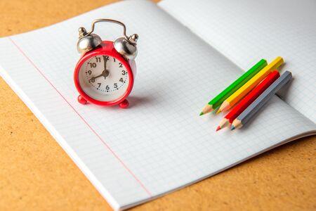 Back to school concept. old alarm clock on a clean notebook. Copy space. Reklamní fotografie