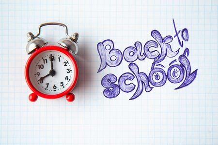 Back to school concept. Old alarm clock on an open notebook
