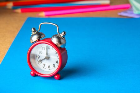 Back to school concept. Old red alarm clock on a blue background. Copy space.