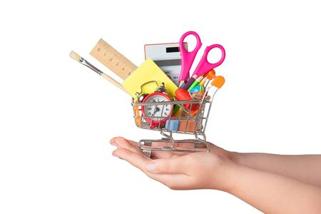 Back to school concept. Bright stationery items in a mini supermarket trolley in hand isolated on white background Stok Fotoğraf