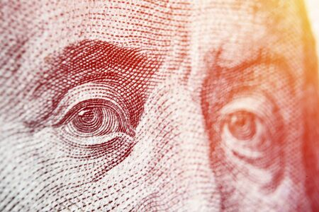Dolar USA close up. Franklin eyes macro. The texture of the fragment of the dollar bill. USD banknote texture. One hundred American dollars. $ 100.