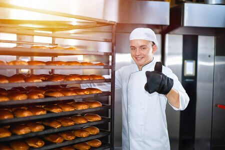 Baker with a hot baking trolley on a background of an industrial oven shows thumb up. Stok Fotoğraf