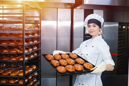 Young girl baker holds a baking tray with hot pastries on the background of an industrial oven in a bakery. Stok Fotoğraf