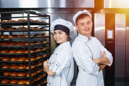Young guy and girl bakers on the background of an industrial oven in a bakery.